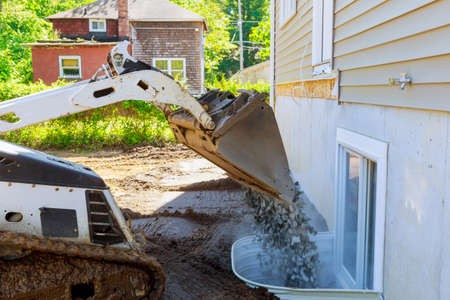 Moving gravel scoop building materials window well for basement construction new residential home