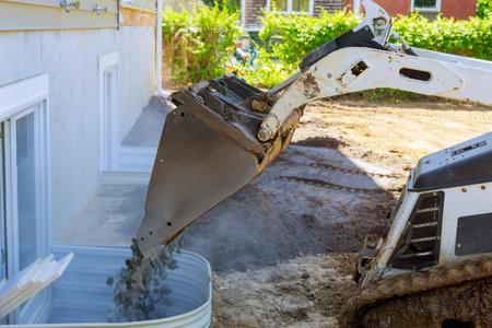 Bucket standing on gravel stones, new house under construction window well craft basement construction Foto de archivo