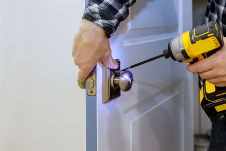 Master with screwdriver installs access the room door new lock in house.