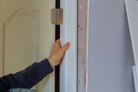 Close up of male installation of interior doors in a interior construction of new housing project