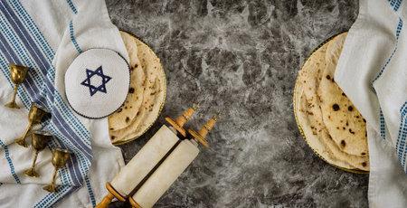 Orthodox Jewish family symbols with cup wine kosher matzah, traditional jewish passover holiday on Holy Scrolls torah