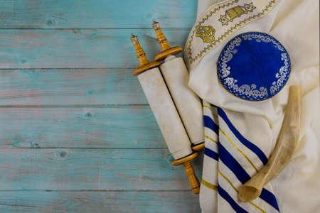 Jewish Orthodox religious symbols prayer book with torah scroll and shofar horn, prayer shawl tallit in a synagogue Stock Photo