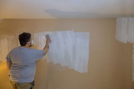 Contractor using sand trowel sanding the drywall Stock Photo