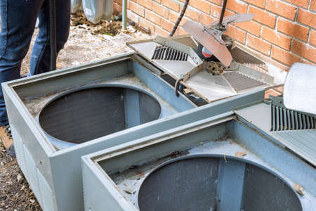 Technical home service with dirty clogged air conditioner condenser cooling fins