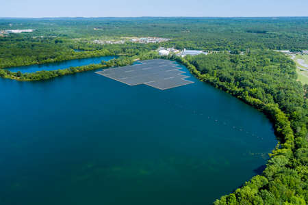 Aerial view of solar power station float on water lake, in the electric renewable ecological energy