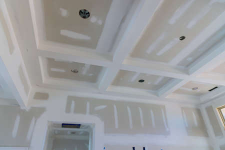 Plastering gypsum drywall seams on the walls and ceiling of a newly house on process of applying layer of putty