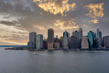 New York City the east river against the lower Manhattan skyline standing tall majestic with the sunset
