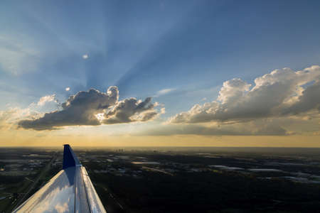 Airplane wing during flight at a wonderful sunset in fluffy clouds 免版税图像