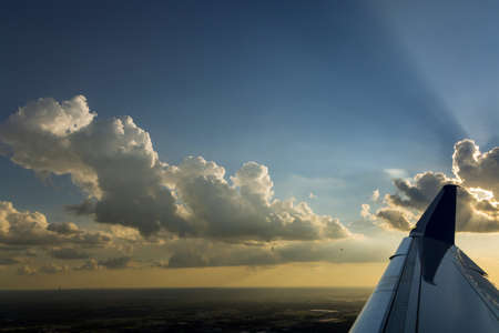 Wing of airline flight plane over dramatic white fluffy clouds on blue sky during sunset. 免版税图像