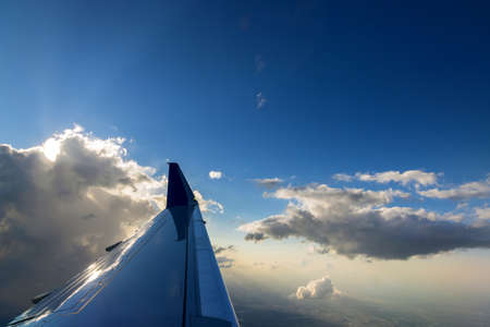 View of the panorama of airplane wing during a beautiful colorful cloudy sunset