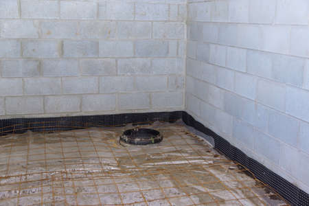 Unfinished view on concrete floor construction of basement empty under construction of residential home 免版税图像