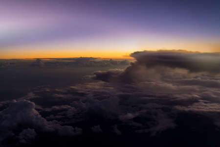 Aerial sunset view over clouds of an aircraft with sunset sky background