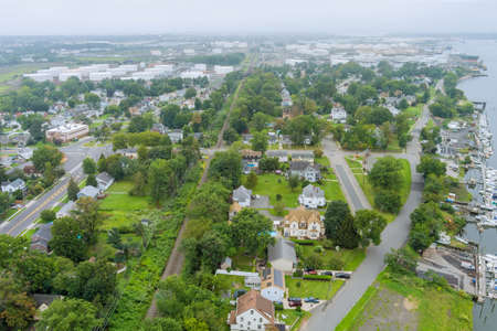 Aerial view over the small town landscape residential sleeping area roof houses in Woodbridge NJ USA near oil refinery industrial tank 免版税图像
