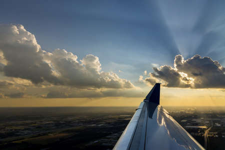 Flight wing of plane over dramatic white fluffy clouds on blue sky during sunset.