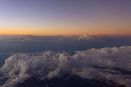 View from airplane beautiful sunset sky above clouds with dramatic light the aircraft window