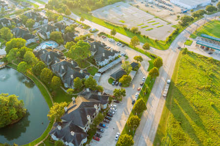 Aerial view of residential suburban housing developments neighborhood during a fall sunset in Houston, Texas, US near pond with tightly packed homes
