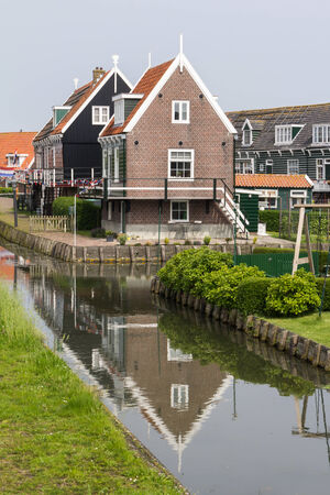 Historic Dutch fishermen village with green wooden houses called Marken photo
