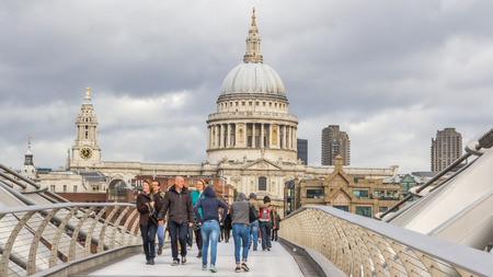Tourists walking across the Milenium bridge to St. Paul Cathedral in London United Kingdom