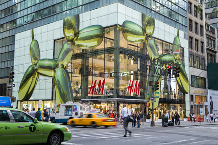 hm: NEW YORK CITY - JULY 29, 2014: Modern H&M shop in 5th street New York City with rushing cabs and people in front.