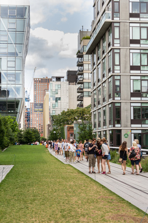 high rises: People walking in High Line Park in New York. The High Line is a public park built on an old railway track elevated above the streets of Manhattan.
