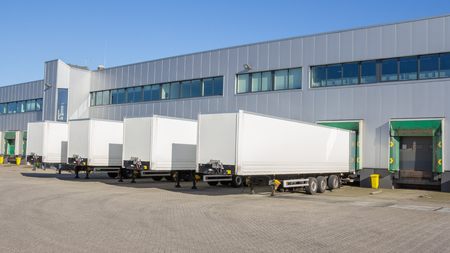 storage warehouse: Trailers at docking stations of a distribution center waiting to be loaded Stock Photo