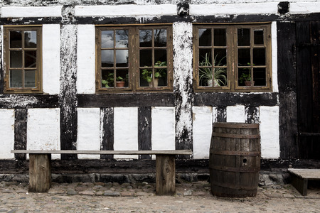 half timbered: White timbered house, with  a bench and rainbarrel  in the old town Den Gamle By in Aarhus Denmark