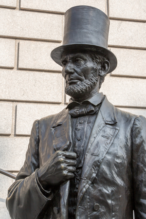 Bronze sculpture of Abraham Lincoln on the stairs in front of a museum in Manhattan, New York.