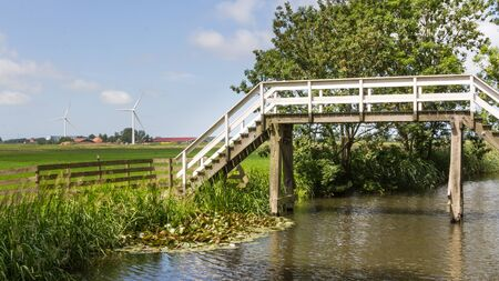 dutch typical: Typical Dutch landscape with an old wooden bridge and modern wind turbines