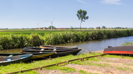 dutch typical: Typical Dutch landscape with wooden rowing boatse and modern wind turbines in the background