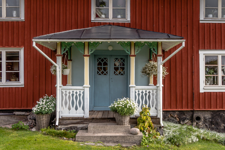 timberland: With flowers decorated facade Rof a ed cottage on the island Harstena in Sweden