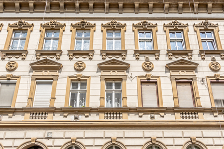 appartment: Facade of an old appartment buidling in Budapest Hungary with round face icons Stock Photo