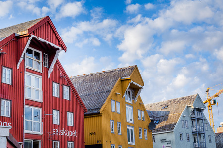 refelction: Old wooden warehousesalong the harbor in the center of Tromso in northerm Norway