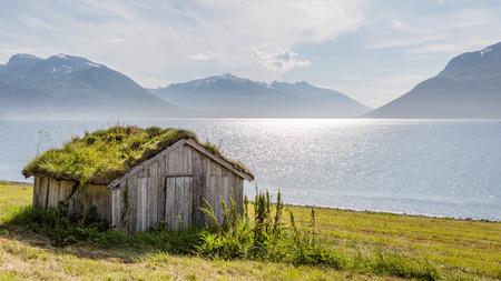 Typisch skandinavische Landschaft mit einer alten Hütte mit einem grünen Dach entlang eines Sees Standard-Bild