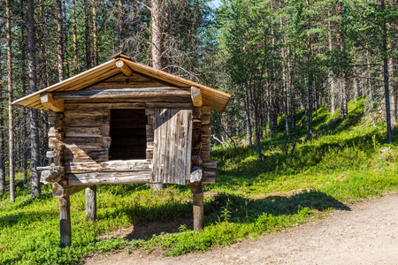 Small traditional  log house on wooden posts in which the Sami in Lapland save their food during winter time.