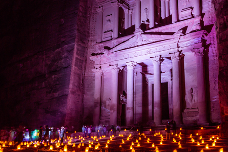 colord: Al Khazneh in the ancient  city of Petra in Jordan at night lighted in different colord and hundreds of candles in the front.