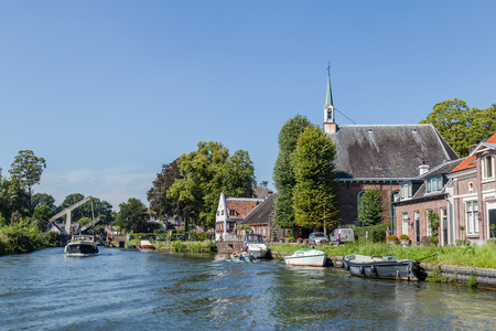 Boating on the river Vecht along the church of Zuilen near Utrecht on summer day