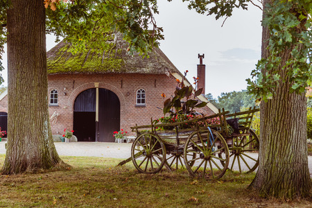 Old farmhouse with a woorden  chariot with flowers in front Stock Photo - 69768369