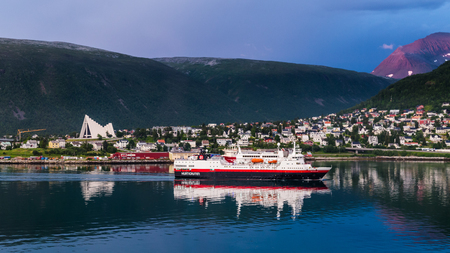 TROMSO, FINLAND - JULY 26, 2016:Skyline with Arctic Cathedral and the Hurtigruten ship navigating into the harbor of  Tromso in northern Norway