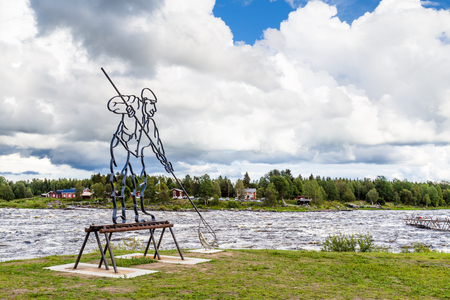 TORNIO, SWEDEN- AUGUST 02, 2016: Sculpture of a whitefish fisherman along the Tornionjoki river on the border of Sweden and Finland Editorial