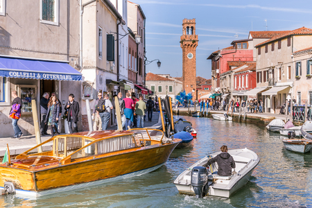 the merchant of venice: Murano Venice, Italy - October 29, 2016: View of the central canal and clock tower on Murano island in Venice Italy. The canal is surrounded with tourist shops selling the famous Murano glass.