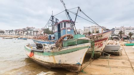 Lagos, Portugal - April, 21, 2017: Dilapidated fishing boats in Lagos Harbor, The Algarve, Portugal