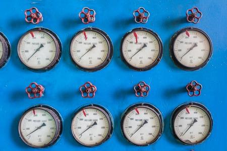 Old pressure meters on a blue metal background