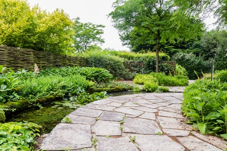 Garden design with water element and rounded flagstones Stockfoto