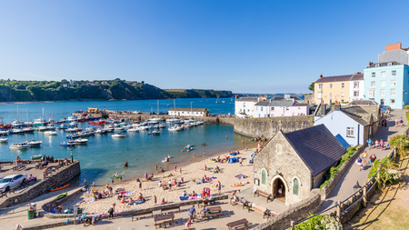 Panoroma of Tenby on a hot summer day, Wales, UK. A picturesque and colorful village on the coast of Wales. Фото со стока - 106696405