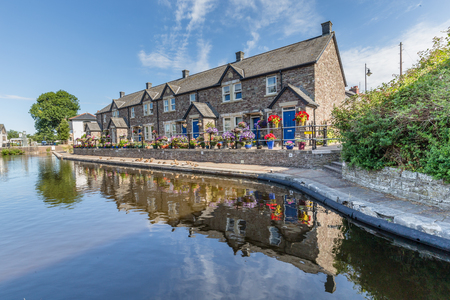 Cottages reflecting in the water of  Brecon Canal basin  in Brecon town, Brecon Beacons National Park, Wales, UK