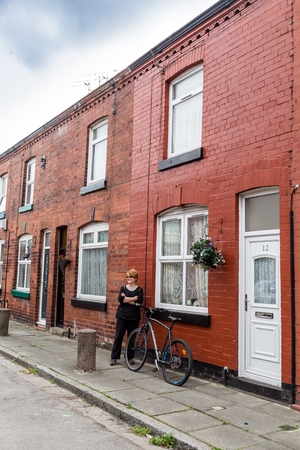 Liverpool, United Kingdom: August 02, 2018: Woman posing in front of the childhood home of Geroge Harrison in Arnold Crove street in Liverpool, Uk