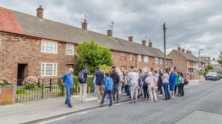 Liverpool, United Kingdom: August 02, 2018: Group of tourist  listening to a guide in front of the childhood home of Sir Paul McCartney on 20 Forthlin Road in Liverpool. Editorial