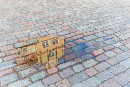 Reflection of an ancient house in a little pond on a cobbled city square after a rain shower Stockfoto - 115482277