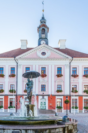 Tartu, Estonia - September 27, 2018: Town hall in the historical  centre of  Tartu in Estonia with the sculpture of kissing studens under an umbrella in front