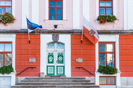Tartu, Estonia - September 27, 2018: Entrance of the Town hall with the flags of Tartu and Estonia in the historical  centre of  Tartu in Estonia